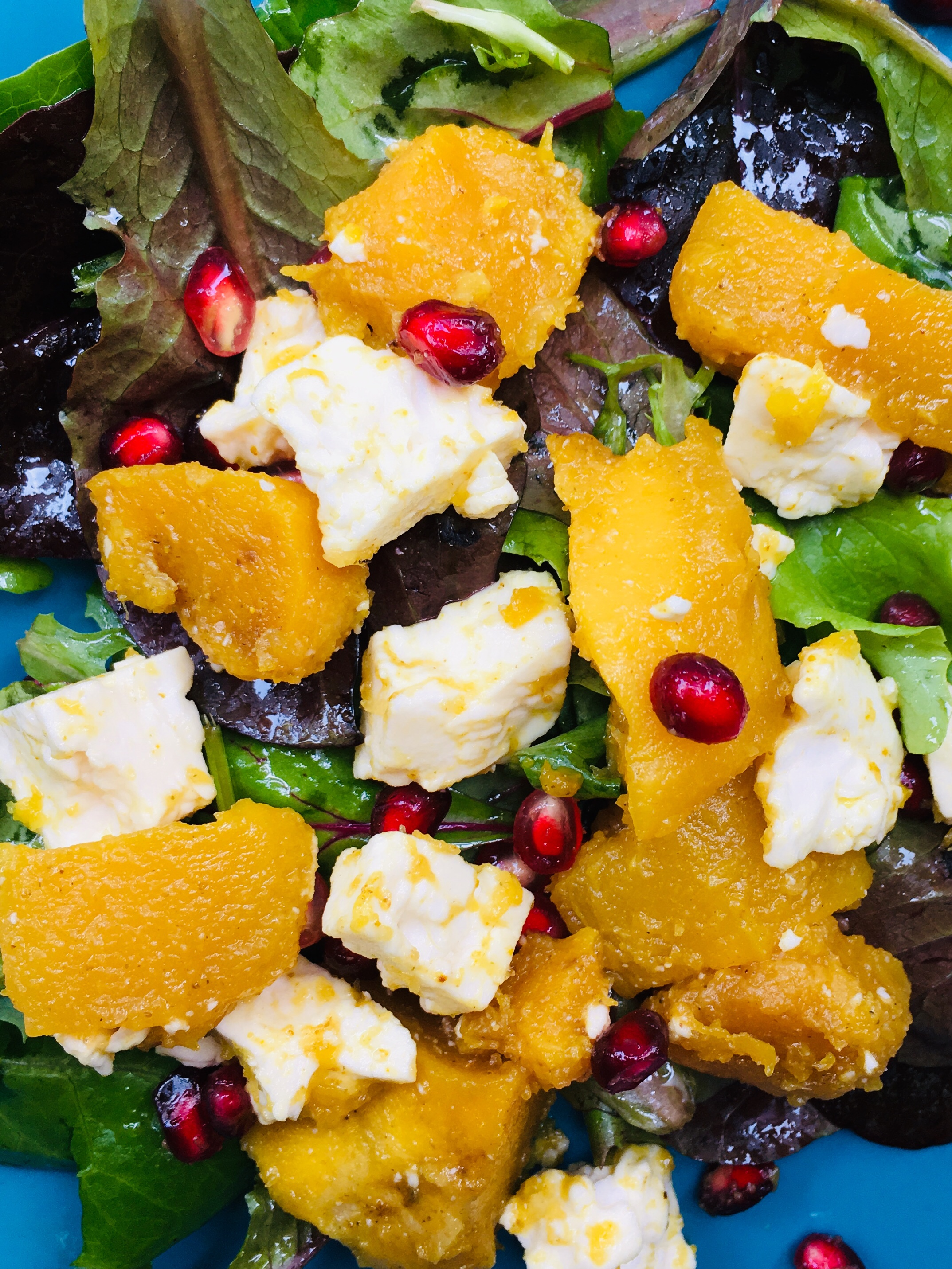 Squash with pomegranate and feta on dressed salad greens