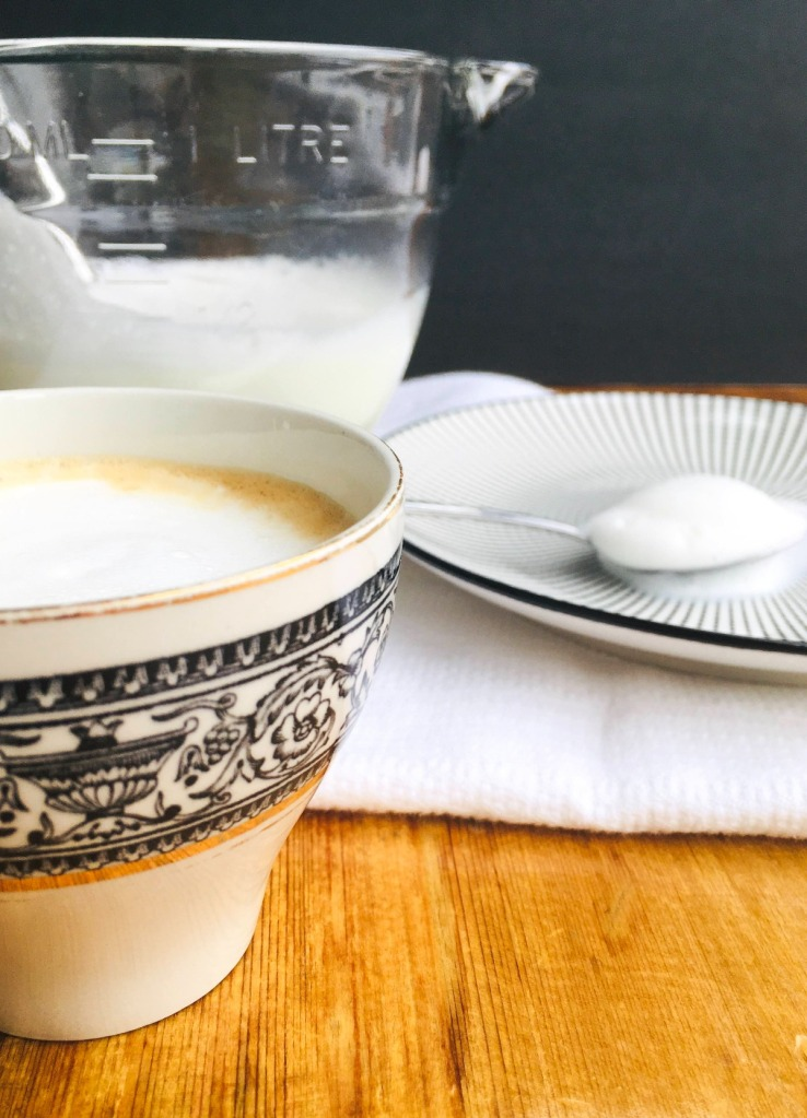 frothy milk and coffee in a measuring cup, spoon and cup of coffee