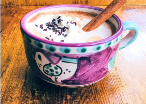 hot chocolate with a cinnamon stick, whipped cream and sprinkles