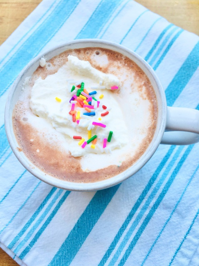 a cup of hot chocolate with whipped cream and rainbow sprinkles
