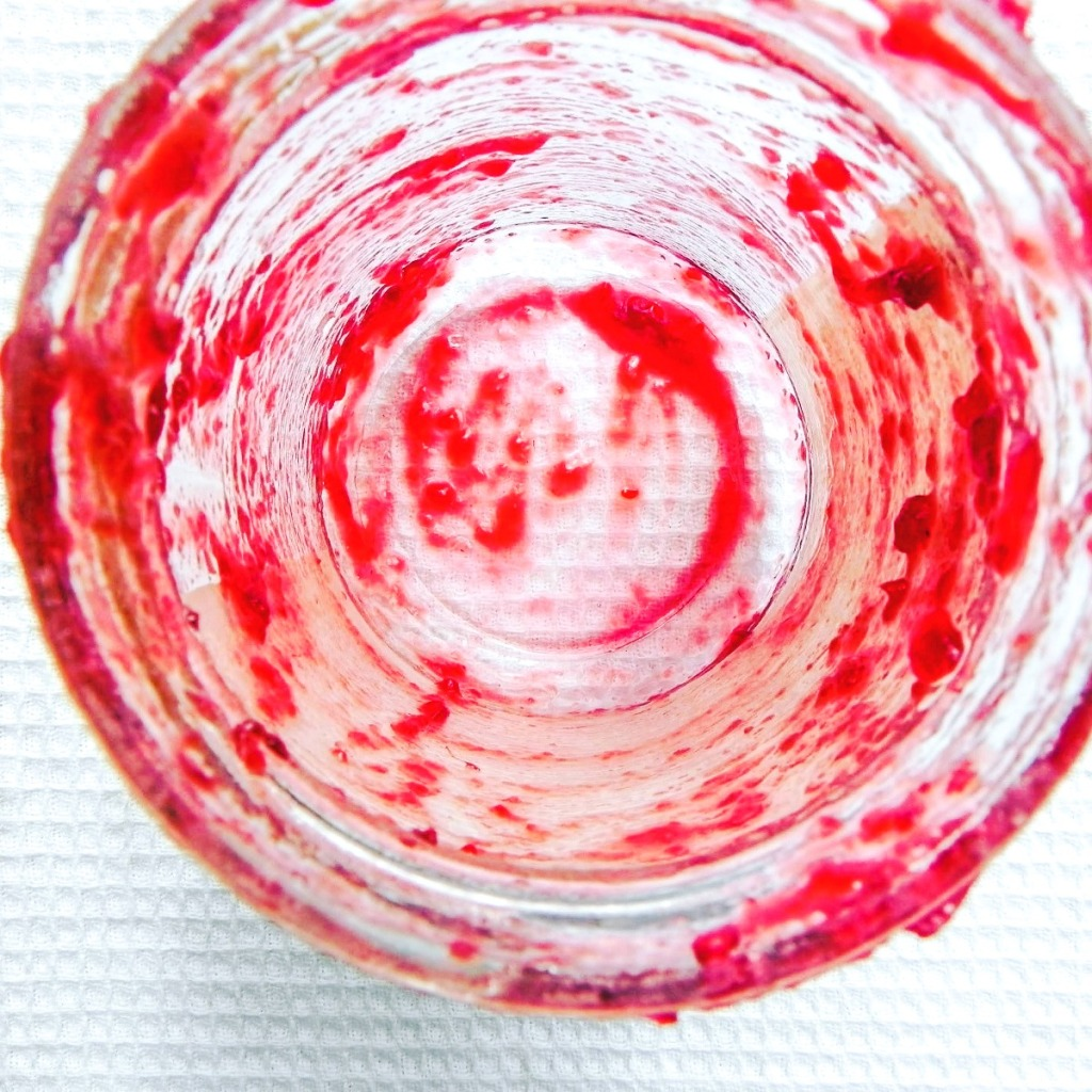 nearly empty jam jar with red jam