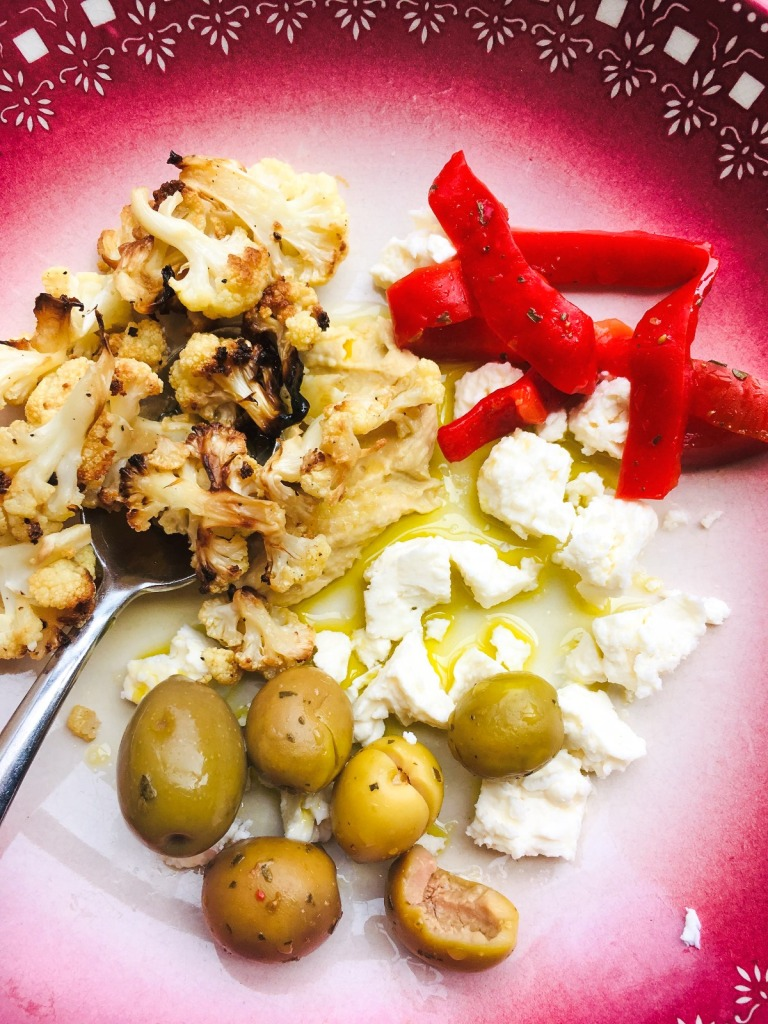 roasted cauliflower, peppers, feta and olives in a shallow dish