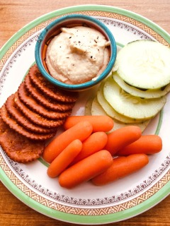 babu carrots, round cucumber slices and crackers with hummus